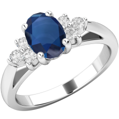 RDS565W - 18ct white gold ring with an oval sapphire centre, and a cluster of 3 round brilliant cut diamonds on either side all in a claw setting..
