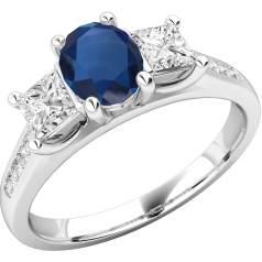RDS568W - 18ct white gold ring with a central oval sapphire and a princess cut diamond either side all in a claw setting, with round brilliant cut diamonds in a channel setting on the shoulders.